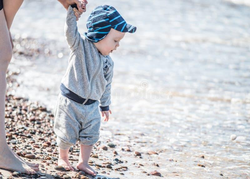 Liten unge nära havet som ser för att bevattna royaltyfria foton