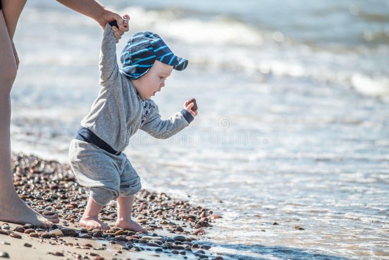 Liten unge nära havet som tappar stenar för att bevattna royaltyfri bild