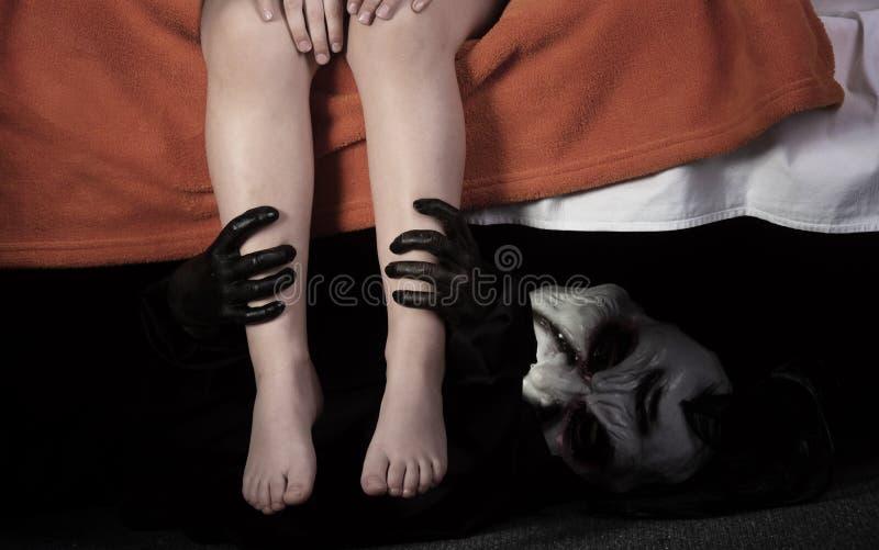 Liten unge och monster under sängen fotografering för bildbyråer