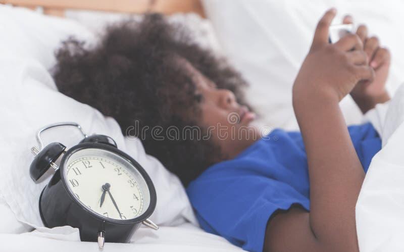 Liten unge som använder smartphonen med ringklockan som räknar tid i morgonen royaltyfri foto