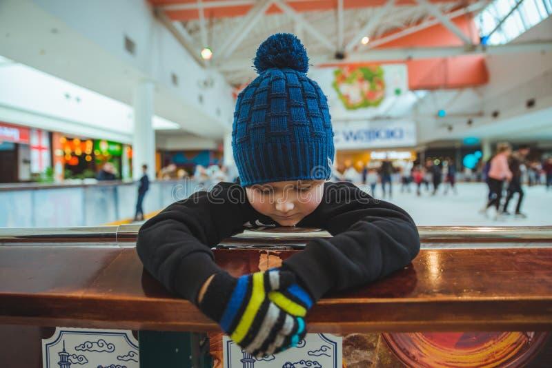 liten unge som lär hur man åker skridskor på isisbanan royaltyfria foton