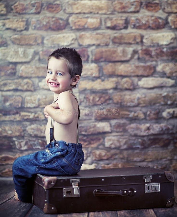 Liten unge som leker på resväskan arkivfoto