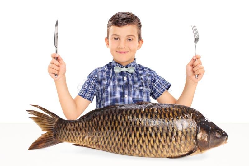 Liten unge som placeras på tabellen med en enorm rå fisk royaltyfri foto