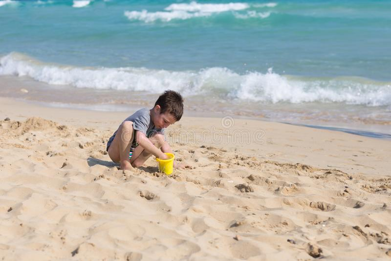Liten unge som spelar med sand på stranden bara Pys nära havet Sommarlek royaltyfri foto