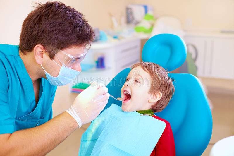Liten unge, tålmodig besöka specialist i tand- klinik royaltyfri bild