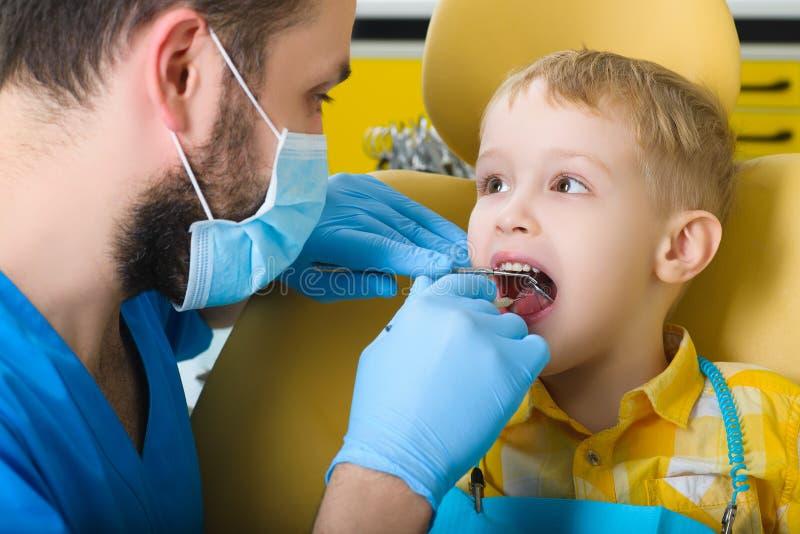 Liten unge, tålmodig besöka specialist i tand- klinik royaltyfria foton