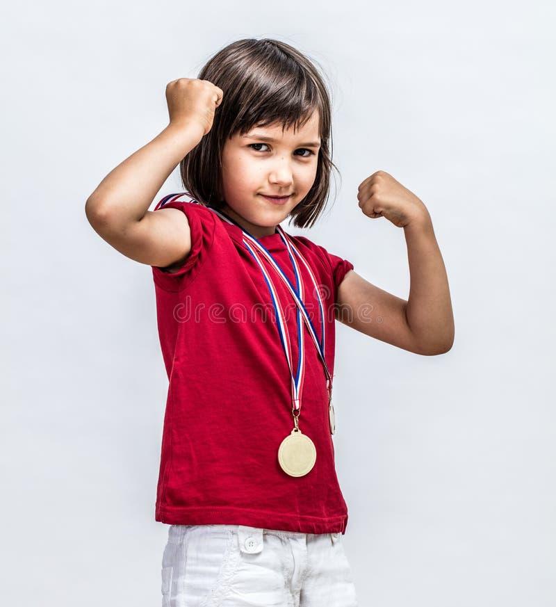 Liten uppnosig flicka med att le för medaljer som visar ung kvinnlig makt arkivbild