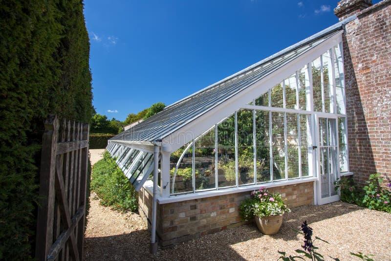 Liten utbyggnadväxthus Härligt engelskt land walled trädgårds- bric royaltyfri bild