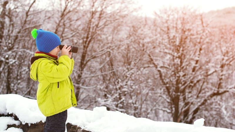 Liten utforskare med monocularen på vinternaturen Utforskare för natur för unge för Ð-¡ ute i semester för vinterskogvinter lyckl royaltyfria foton