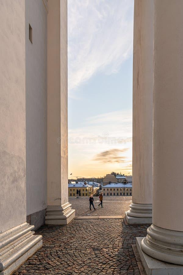 Liten vertikal vy av personer mellan höga kolumner och solnedgång royaltyfri bild