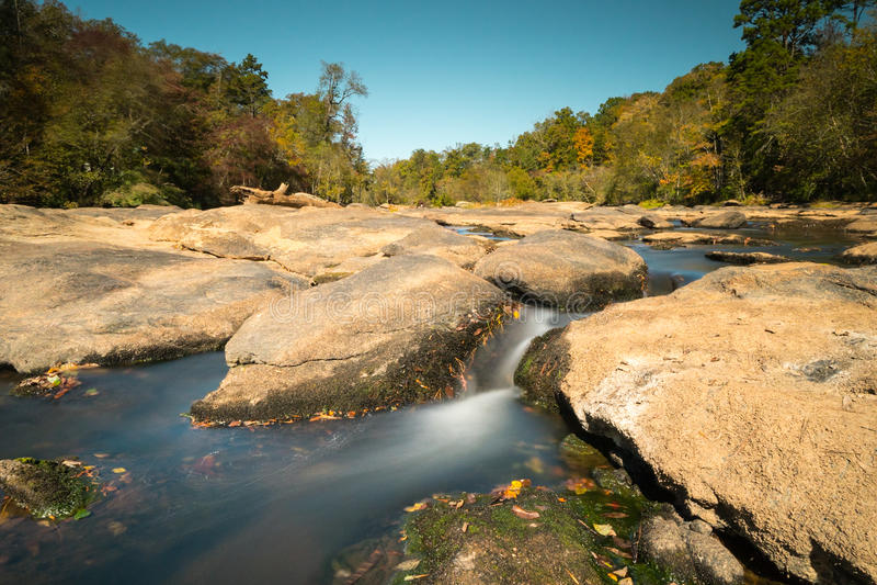 Liten vik och vaggat med den släta floden och nedgångskogen arkivbild