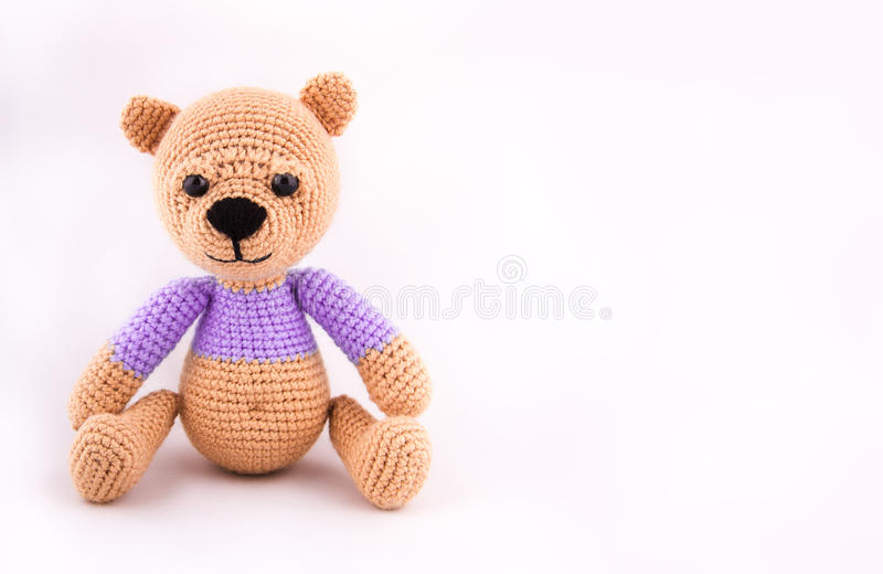 Liten virkad nallebjörn på en grå bakgrund En mjuk björngröngöling i lila kläder kopiera avstånd royaltyfria foton
