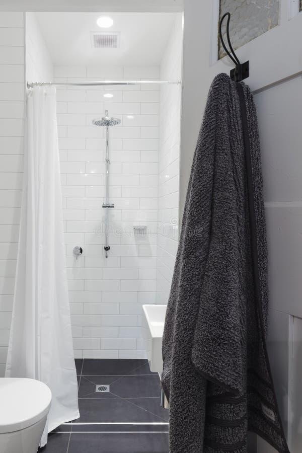 Liten vit belade med tegel ensuitebadrummet med duschen och toaletten och mummel arkivbilder
