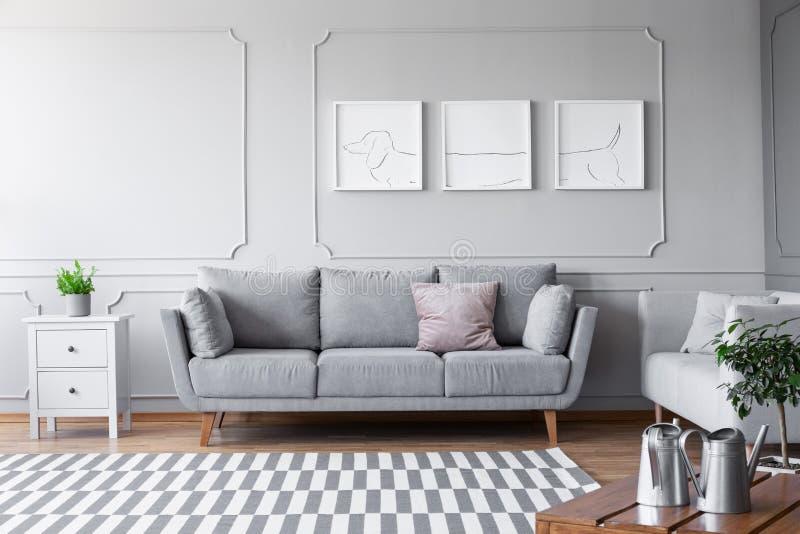 Liten vit byrå med den gröna växten i grå kruka på till av den bredvid den bekväma soffan med kuddar i scandinavian vardagsrum, r arkivbild