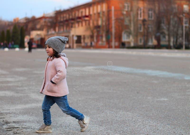 liten vit flicka som går ner gatan i aftonen Stående på bakgrunden av solnedgångcityscapen royaltyfri fotografi