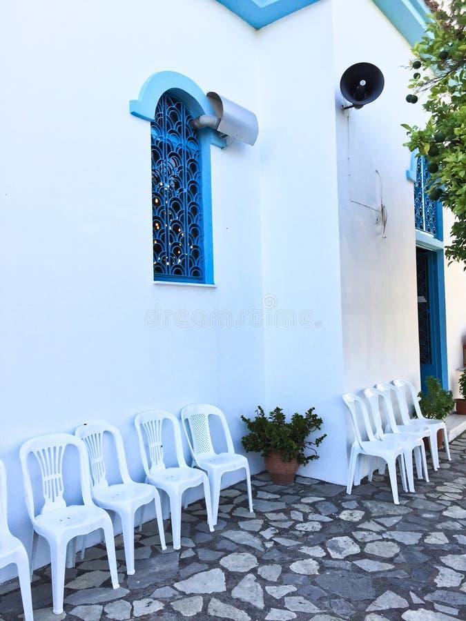 Liten vit grekisk ortodox kyrka; Yttersida med vita plast- stolar royaltyfri bild