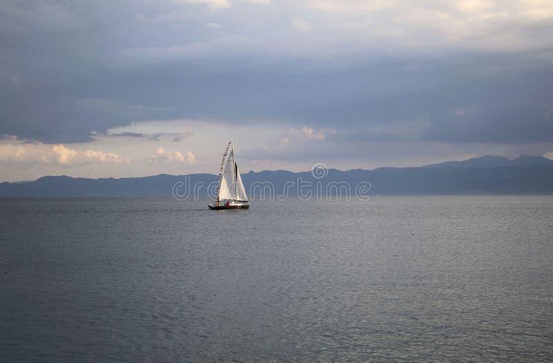 Liten vit segelbåt i stormigt väder på den härliga sjön Ohrid, republik av norr Makedonien royaltyfri bild