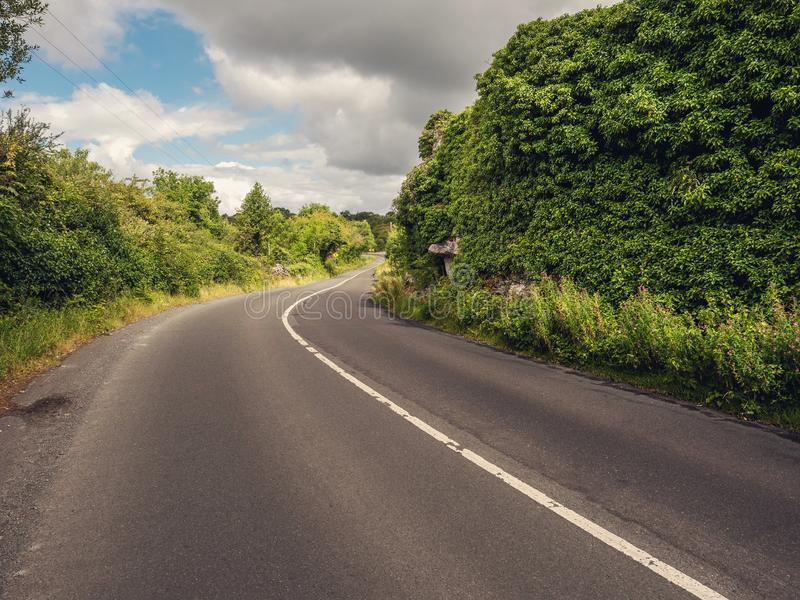 Liten vriden landsväg med skarp vänd, molnig himmel, landssida royaltyfri fotografi