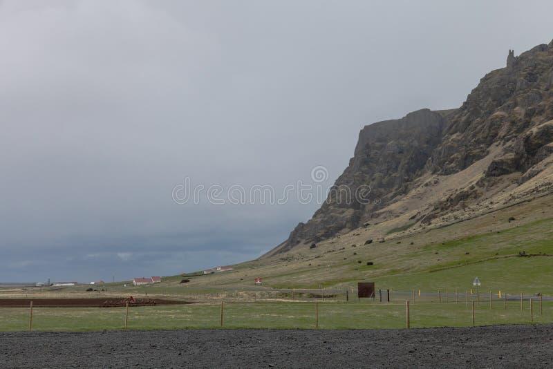 Liten willage få hus på ett stenigt landskap för stenigt berg av Island arkivfoto