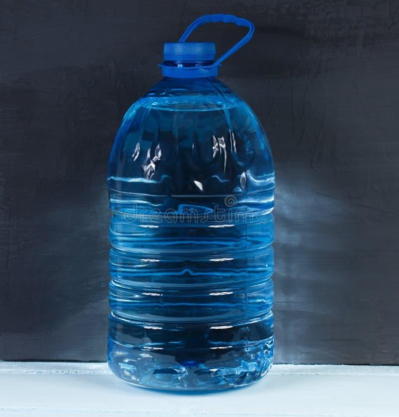 5 liter Grote plastic fles drinkbaar water op een donkere backgrou stock afbeelding