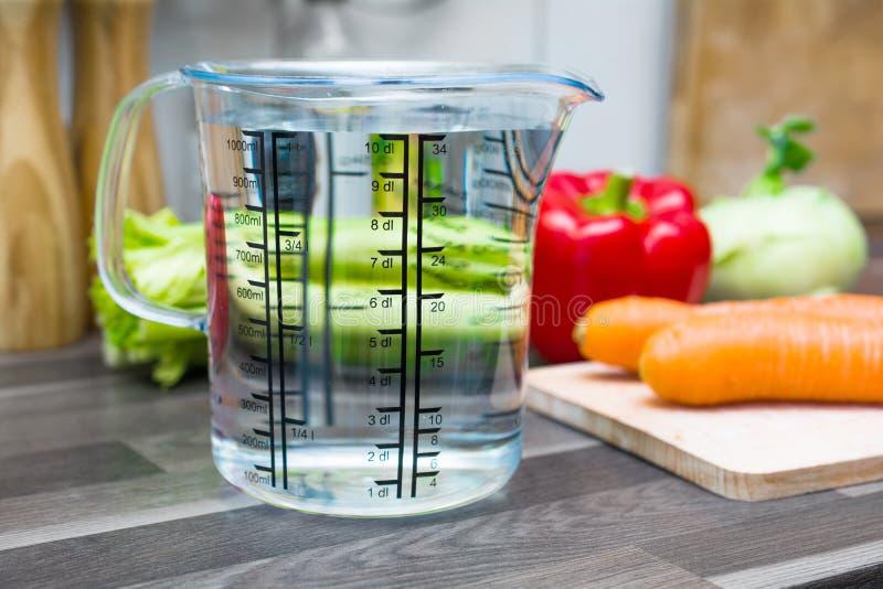 1 liter/1000ml/10dl av vatten i A som mäter koppen på en diskbänk med grönsaker arkivfoto