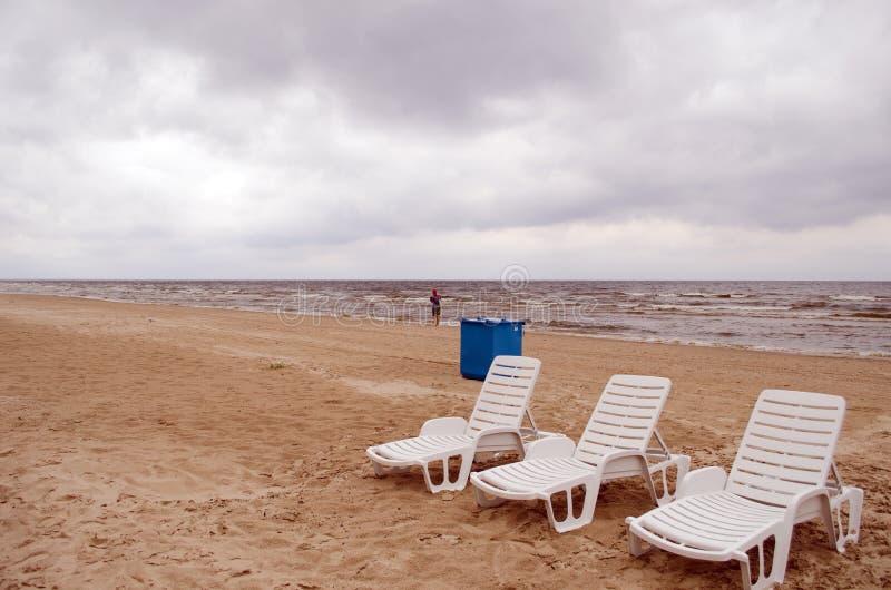 Litera vacía de la choza en caminata de la mujer del cubo de la basura del arena de mar fotos de archivo libres de regalías
