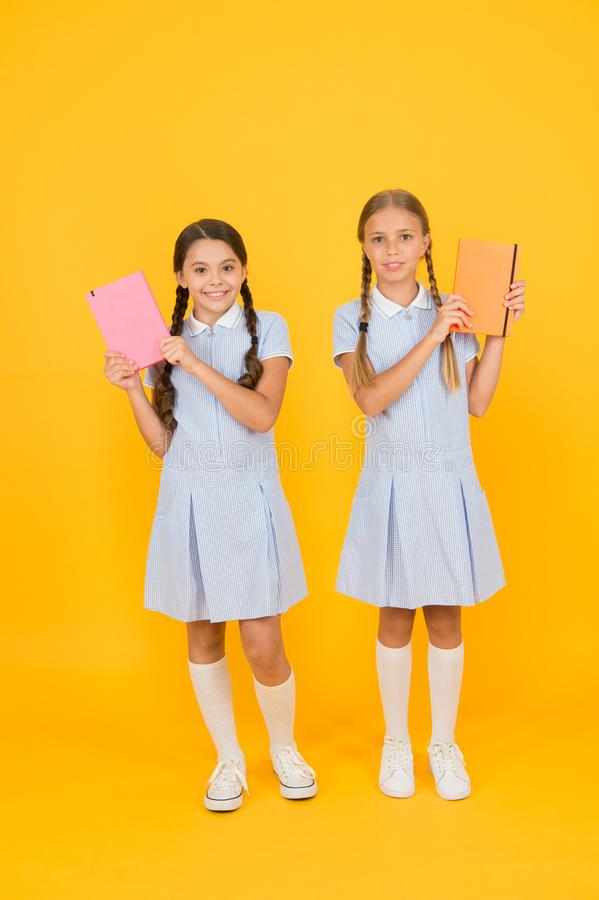 Literacy club. Cute children holding books on yellow background. Little girls with encyclopedia or childrens books. Educational books for schools. Reading royalty free stock photo