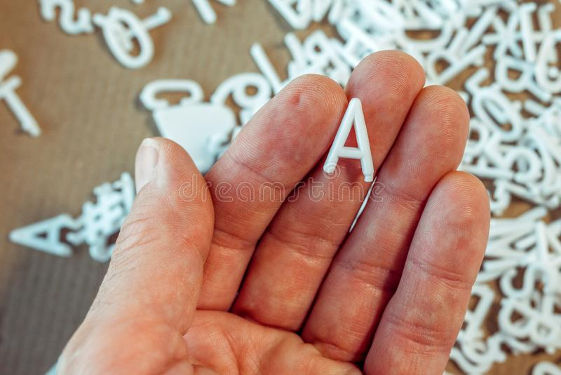 Literacy concept. Male hand holding letter A stock images