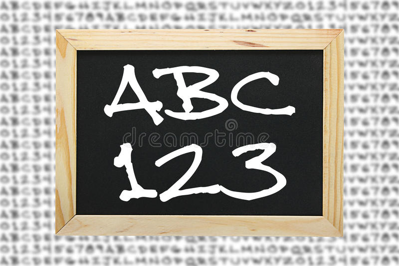 Literacy and numeracy. Image of a black slate with a white wood frame with letters and numerals written on it to illustrate the concept of Literacy and Numeracy royalty free stock photo