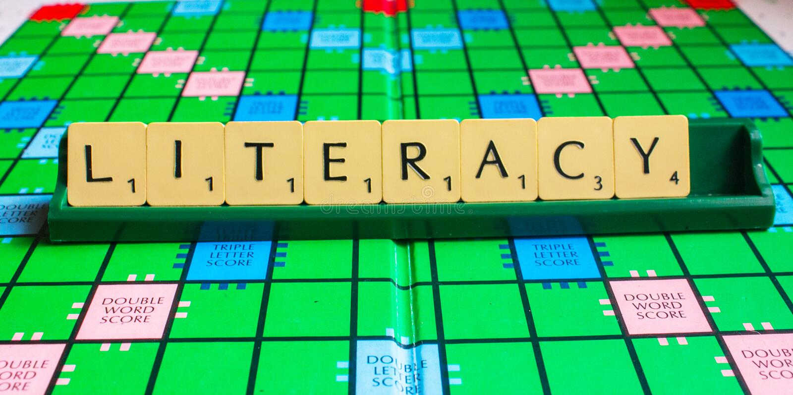 Literacy word on scrabble for use with designs. Literacy words on scrabble for use with designs or as wallpaper background stock image
