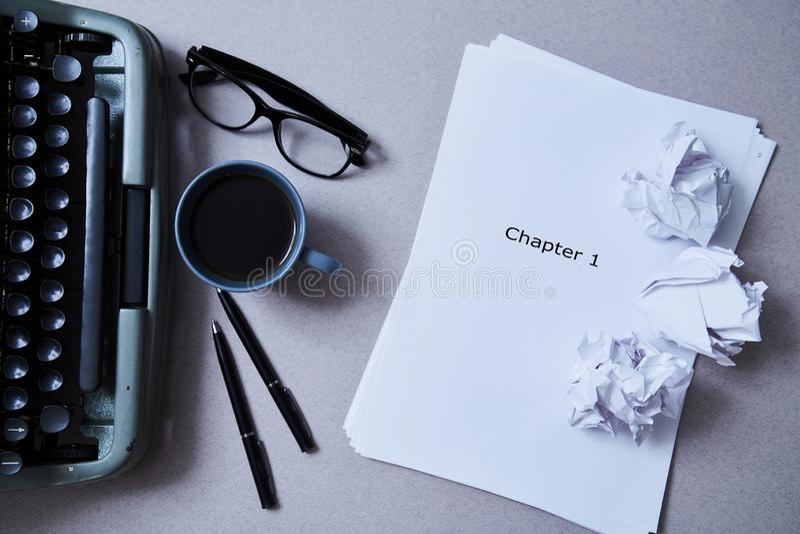 Literatur-, Autorn- und Verfasser-, Schreibens- und Journalismuskonzept: Schreibmaschine, Tasse Kaffee und Gläser und ein Papier lizenzfreie stockfotografie