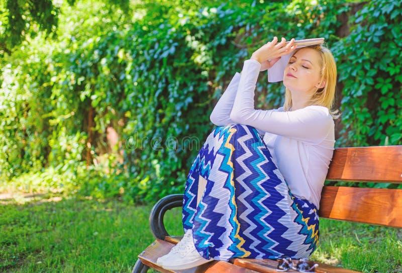 Literatura aburrida La mujer cansó la rotura rubia de la toma de la cara que se relajaba en libro de lectura del jardín El estudi fotos de archivo libres de regalías