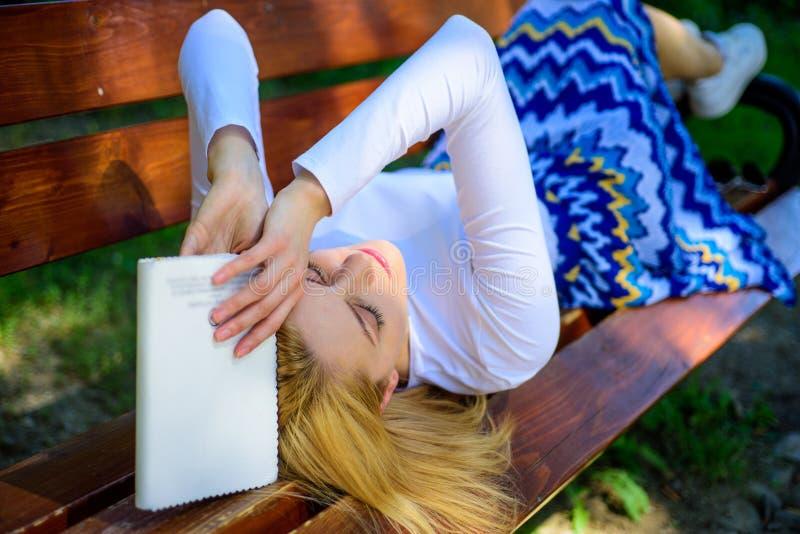 Literatura aburrida Prepárese para la rotura cansada mujer de la toma de la cara de la prueba que se relaja en libro de lectura d imágenes de archivo libres de regalías