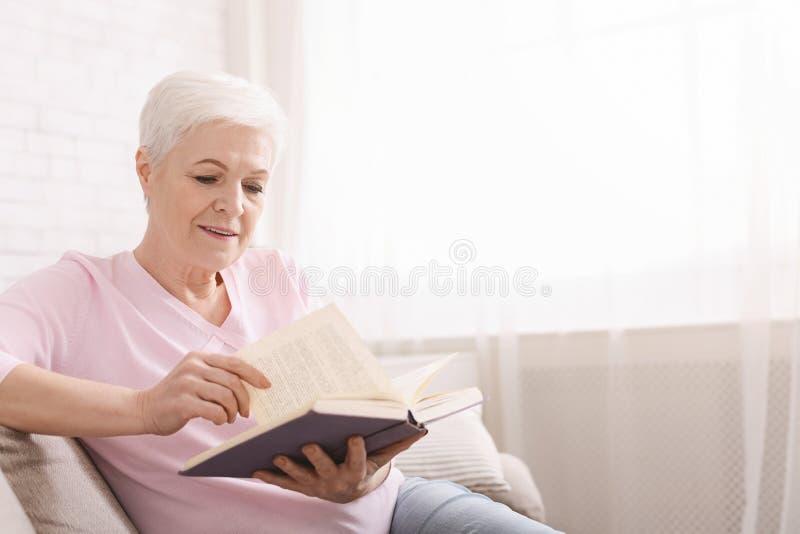 Literatura madura del negocio de la lectura de la mujer en casa imágenes de archivo libres de regalías