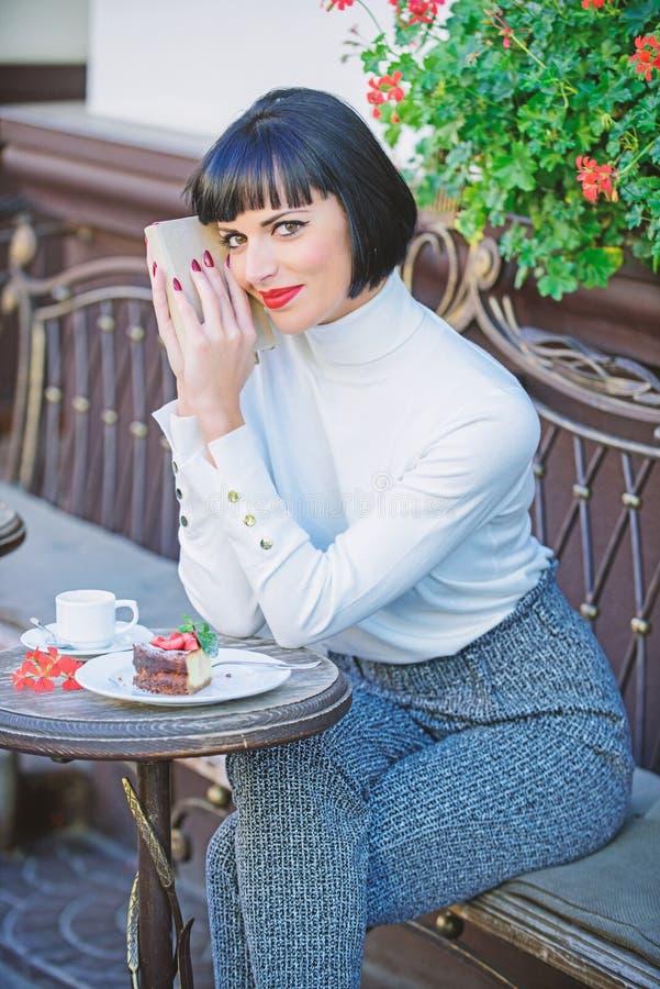 Literatura moderna para la hembra La señora del negocio leyó el libro durante descanso para tomar café Café y buen libro para el  imagen de archivo libre de regalías
