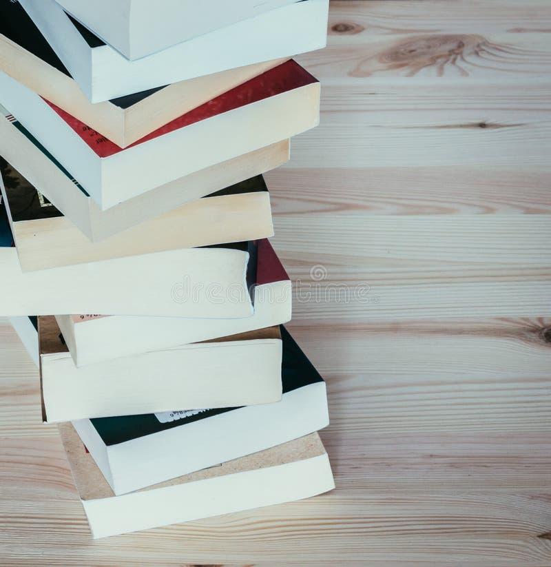 Literatura para o estudo: Pilha de livros na placa de madeira fotografia de stock