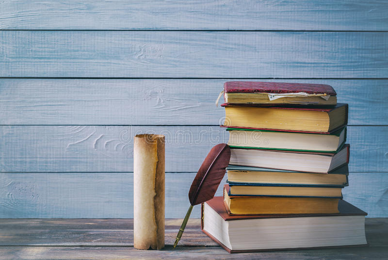 Literature concept. Brown feather near old scroll and stack of old books against blue wooden background.  royalty free stock images