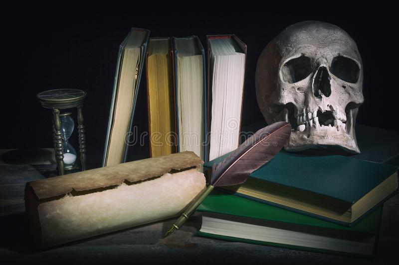 Literature concept. Old books with skull near scroll, quill feather pen and vintage hourglass. royalty free stock photography