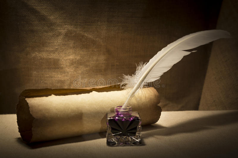 Literature concept. Old inkstand with feather near scroll on canvas background.  stock photography