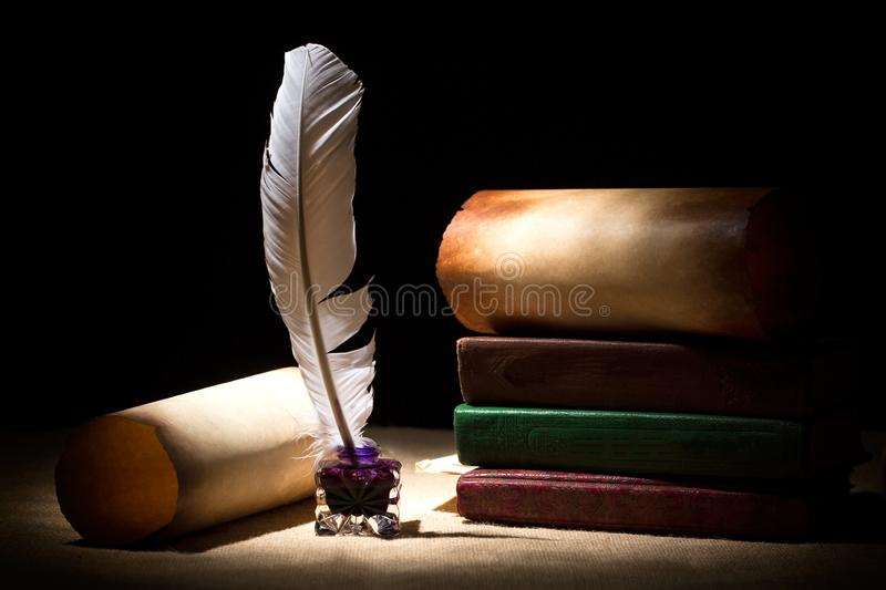 Literature concept. Old inkstand with feather near scrolls and books against black background. Dramatic light.  royalty free stock images