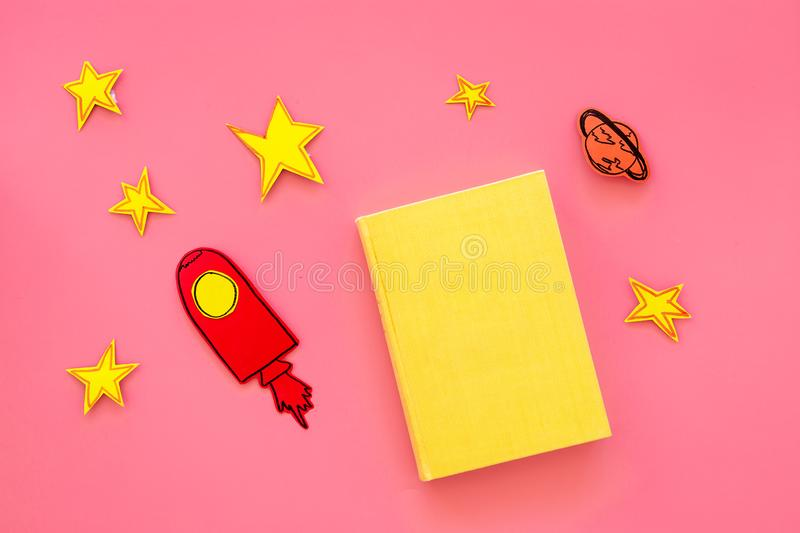 Literature about cosmos for school children. Book with blank cover near cutout of rocket, stars, moon on pink background. Top view mockup royalty free stock photo