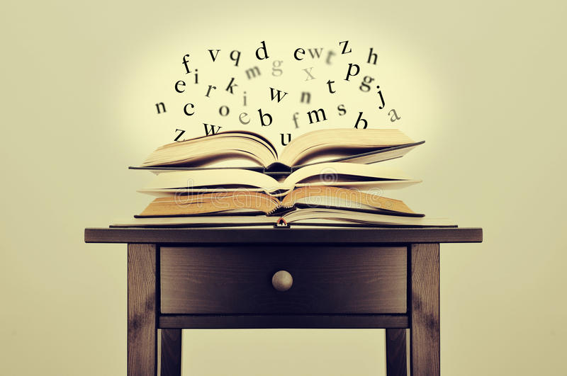 Literature or knowledge. A pile of books and letters floating over them on a desk symbolizing the idea of literature or knowledge stock images