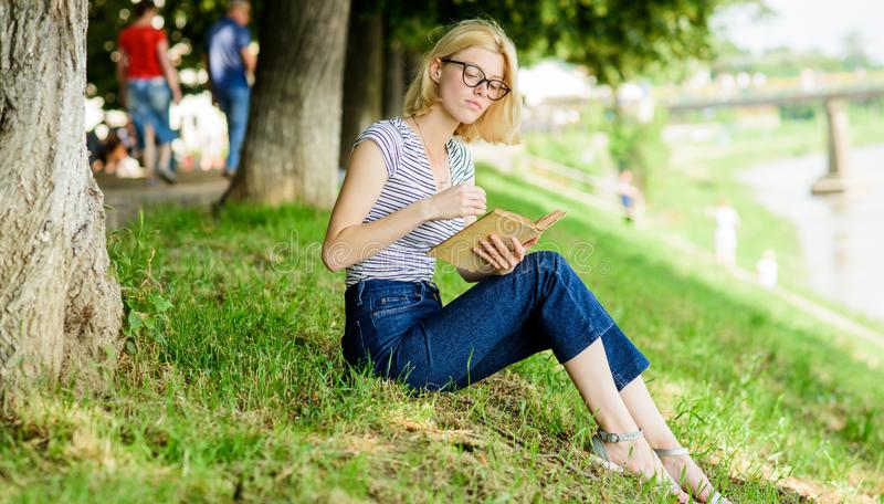 Literature for summer vacation. Girl relaxing at riverside after working day. Rest relax and hobby. Woman dreaming about royalty free stock photos