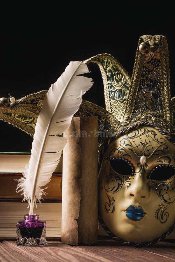Literatury pojęcie Kałamarz z piórkową pobliską venetian maską, książkami i starą ślimacznicą na czarnym tle, fotografia royalty free