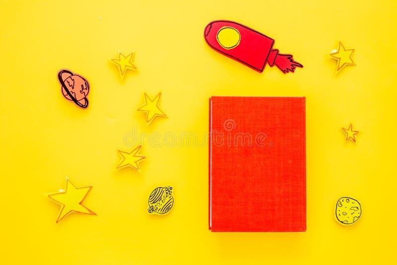 Literatuur voor kinderen Fantactic, fictieverhaal Boek met lege dekking dichtbij knipsel van raket, sterren, maan op geel stock afbeelding