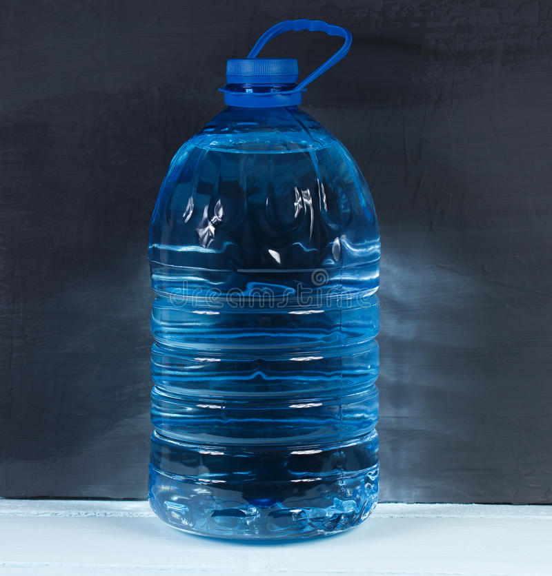 5 liters. Big plastic bottle of potable water on a dark background. 5 liters. Big plastic bottle of potable water, barrel with handle on a dark background stock image