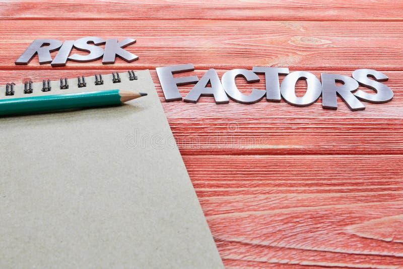 Litery żelaza czynniki ryzyka z notebookiem i zielonym ołówkiem fotografia stock
