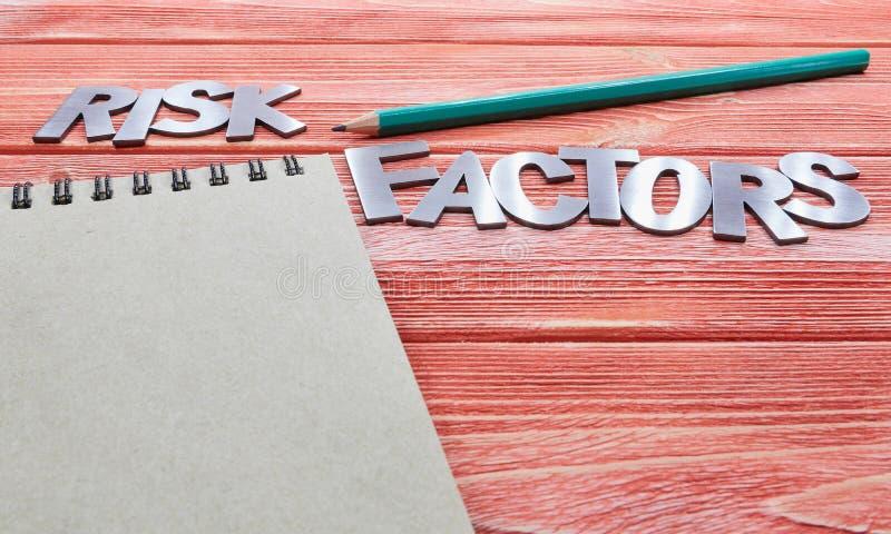 Litery żelaza czynniki ryzyka z notebookiem i zielonym ołówkiem zdjęcia stock