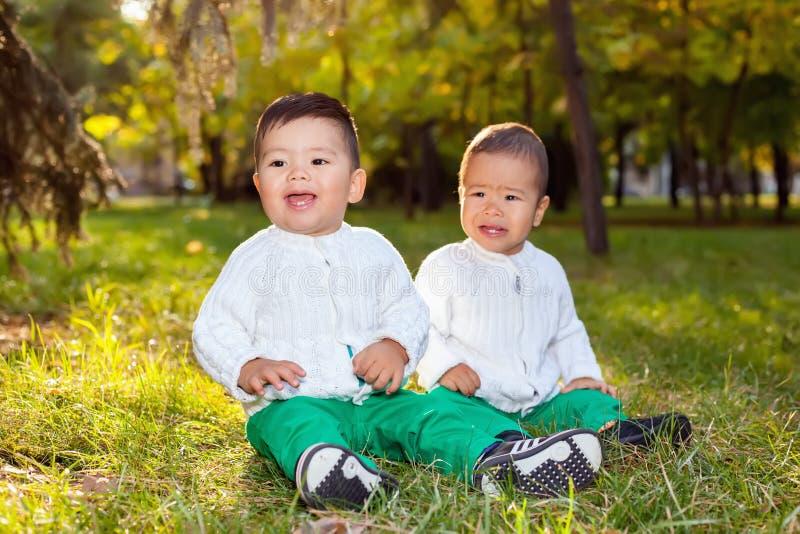 Litet asiatiskt barn som två spelar i parkera som sitter på gräset fotografering för bildbyråer