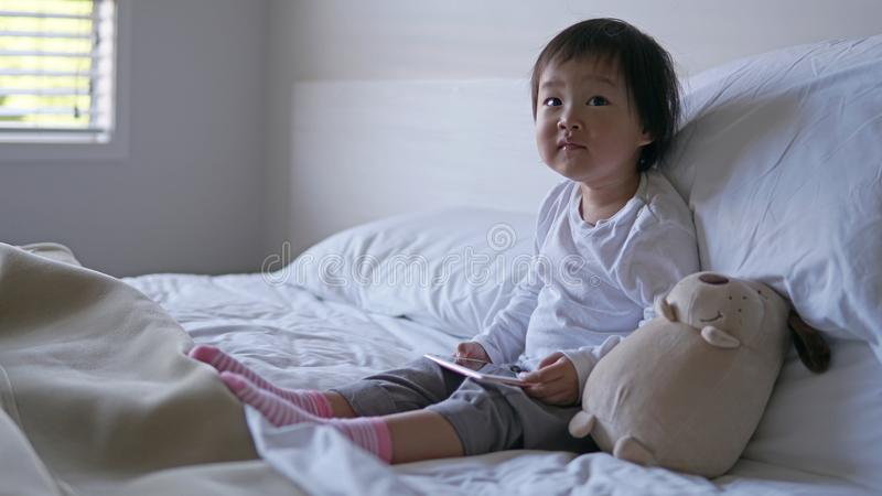 Litet asiatiskt kinesiskt litet barnsammanträde på sängen missbrukade till ipad royaltyfri bild